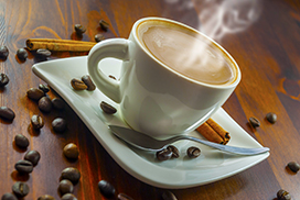hot cup of coffee and cinnamon on wood table